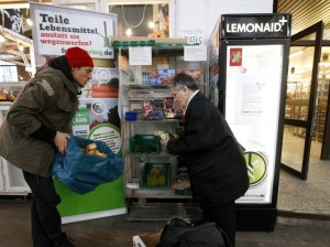 Raphael Fellmer (L), a supporter of the foodsharing movement brings food sorted out from waste bins of an organic supermarket to a distribution point at the indoor market Markthalle Neun (indoor market nine) as a woman takes a piece of bread in Berlin, January 31, 2013. Foodsharing is a German internet based platform where individuals, retailers or producers have the possibility of offering surplus food to consumers for free. Picture taken January 31.   TO MATCH STORY GERMANY-FOODSHARING/    REUTERS/Fabrizio Bensch (GERMANY  - Tags: FOOD POLITICS SOCIETY) - RTR3DGCF