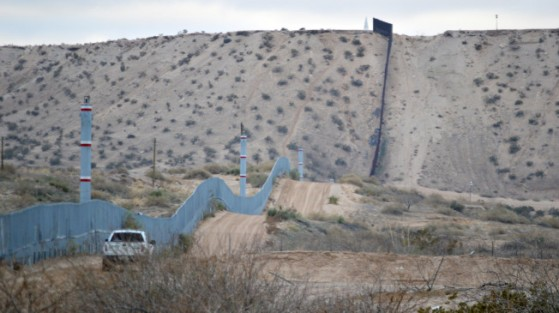FILE - In this Jan. 4, 2016 photo, a U.S. Border Patrol agent drives near the U.S.-Mexico border fence in Sunland Park, N.M. Can Donald Trump really make good on his promise to build a wall along the 2,000-mile U.S.-Mexican border to prevent illegal migration? What's more, can he make Mexico pay for it? Sure, he can build it, but it's not nearly as simple as he says. (AP Photo/Russell Contreras)